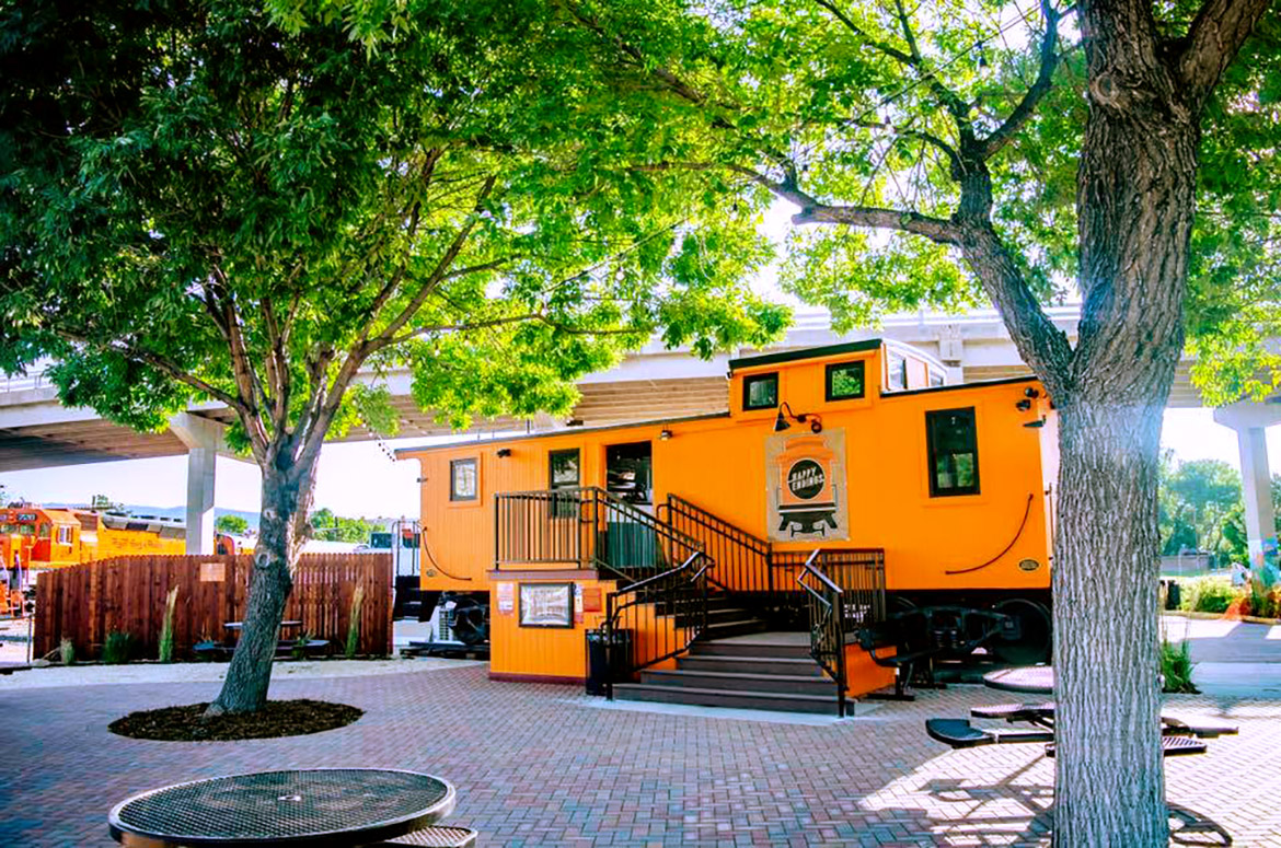 orange caboose cafe behind two trees